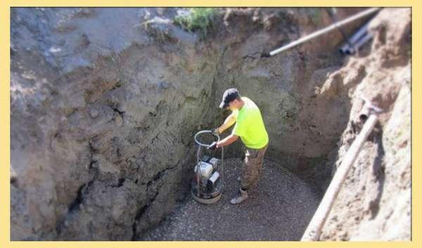 Утрамбовка песка в яме под септик